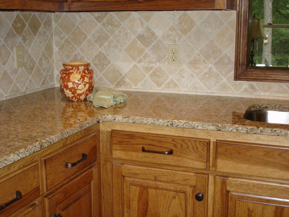heres a simple beige colored kitchen backsplash with a granite countertop and oak cabinets description
