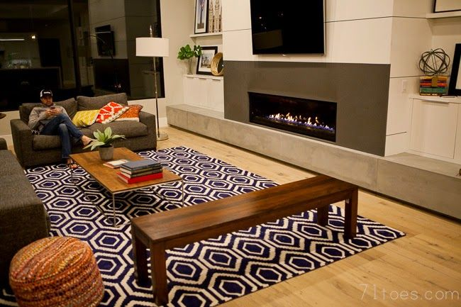 love the gray couches, the wood accents, the fireplace.