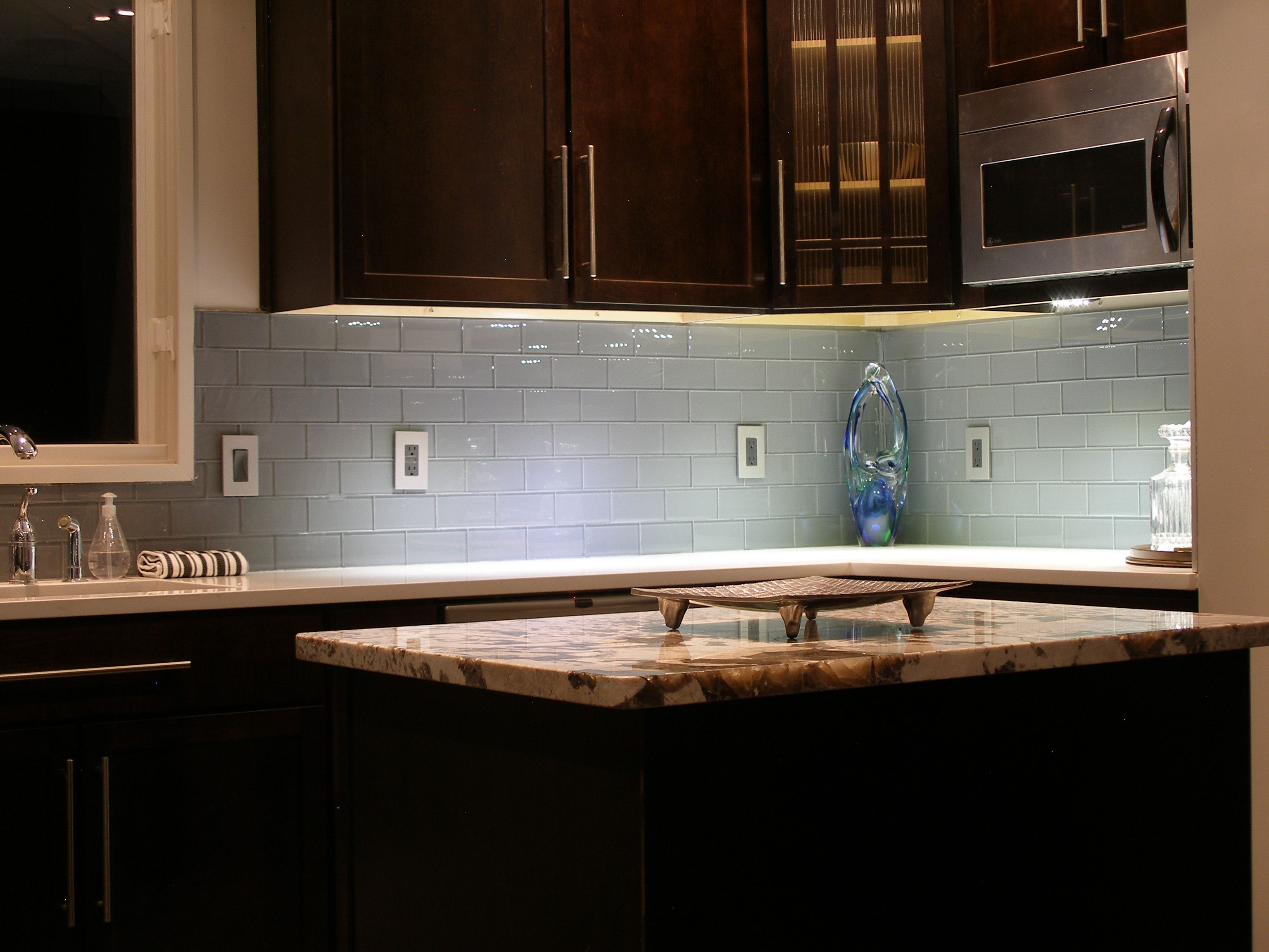 Swish Glass Subway Tile Soft Blue Backsplash With Brown Wooden Kitchen Cabinet Also White Marble Countertop