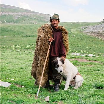 Portrait of shepherd wearing sheepskin cloak, wearing green hat, holding stick standing with sheepdog against background of Urdele Pass, Carpathian Mountains, #Romania, July 2006.
