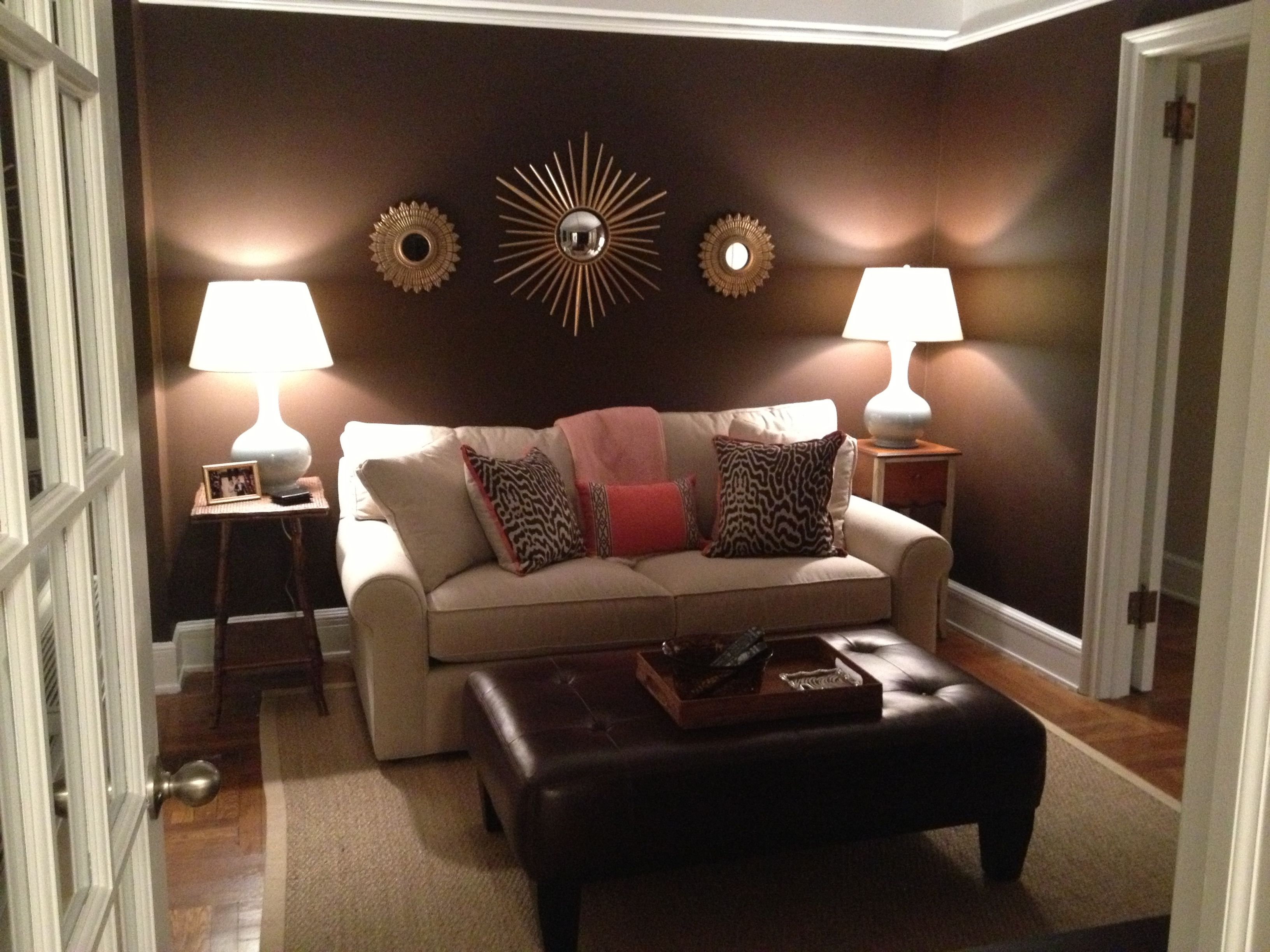 Den-Brown walls with accents of coral and blue create a ...