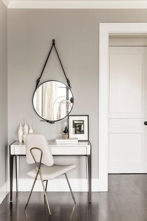 A Jonathan Adler Maxine Chair sits on a stained oak floor at a white modern dressing table finished with wood legs.