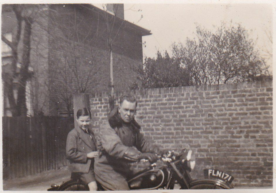 Vintage photograph of father and son on a classic BMW motorcycle, circa 1950s