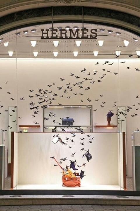 Flying birds lead the viewer to the perch of shoes near a handbag