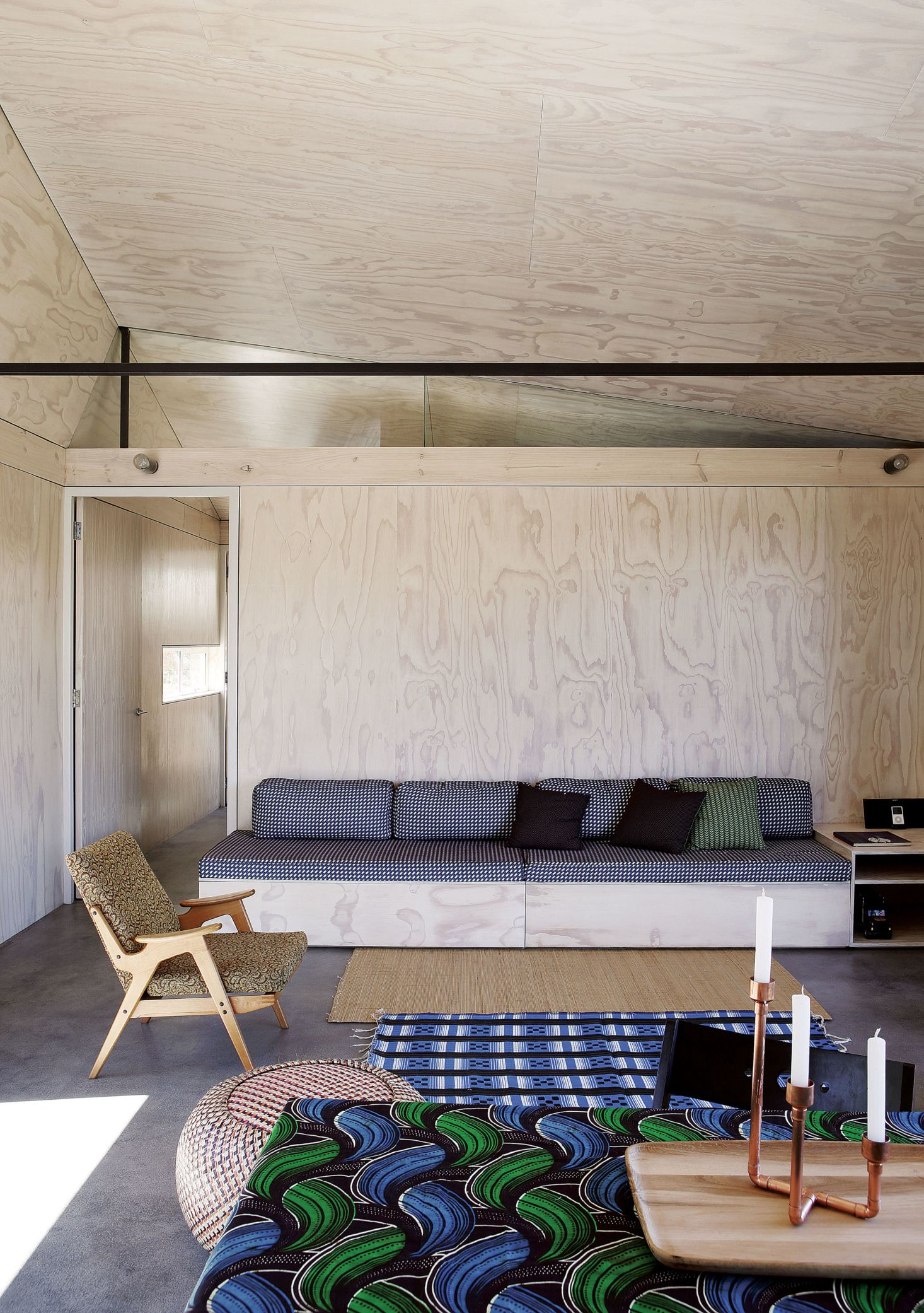 A built in plywood bench upholstered with a checked fabric anchors the living space
