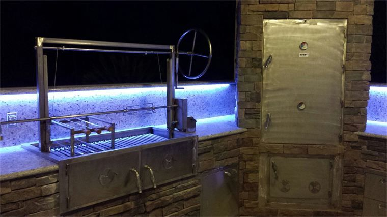 DROP IN UNIT AND SMOKER INSTALLED IN AN OUTDOOR KITCHEN, SHOWN AT NIGHT WITH INSTALLED LIGHTING