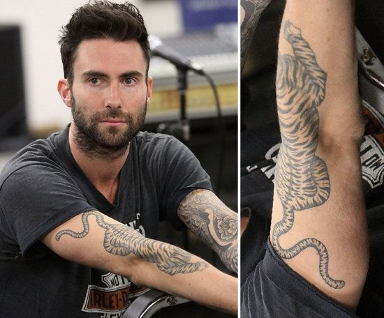 2ddbf66d3 Adam Levine has a tattoo sleeve on his left arm and a large tiger design  placed on his right forearm.
