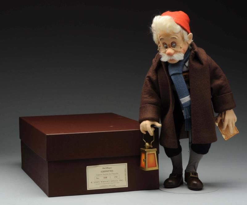 """This remarkable edition has extraordinary attention to detail and is seldom seen on the secondary market.  Lifelike Geppetto is made from molded felt, is fully jointed, and stands 18"""" tall.  He wears black pants, a shirt, a red hat, blue scarf, and brown felt coat. He holds a lantern in one hand and a miniature book in the other. The doll is tagged 9/250.  He was made in 1996 and designed and produced in association with Disney.  Condition:  As noted. This item is complete and in excellent…"""