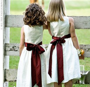 9ff75a6ae Wine-colored sashes matched the bridesmaid dresses and added a touch of  color to the flower girls' ivory dresses. Love this.