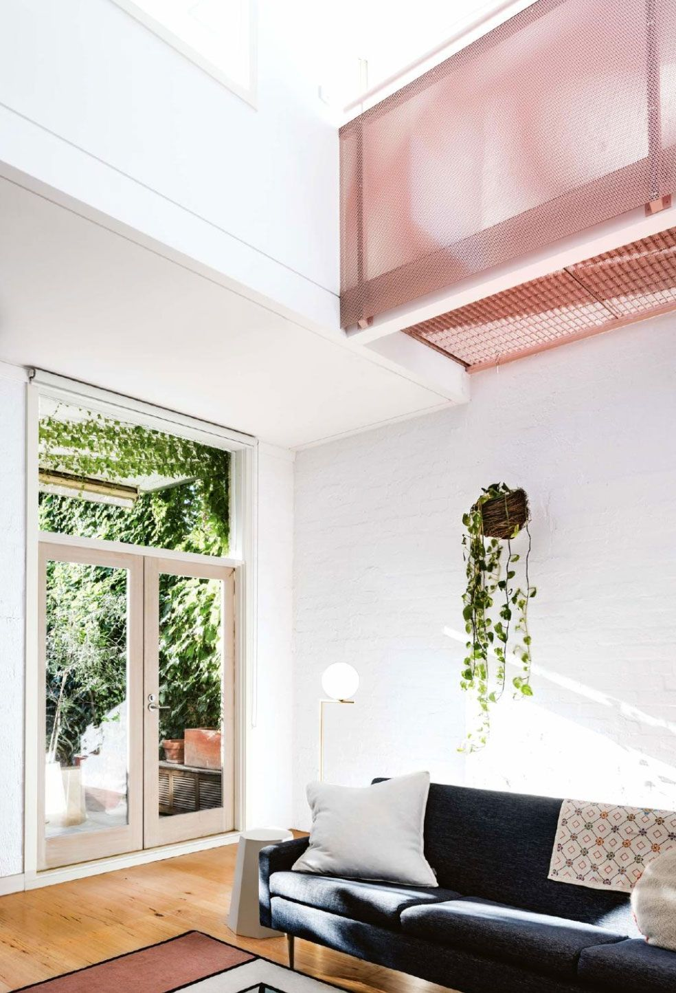 living room with pale pink paint and green plants with white walls ...