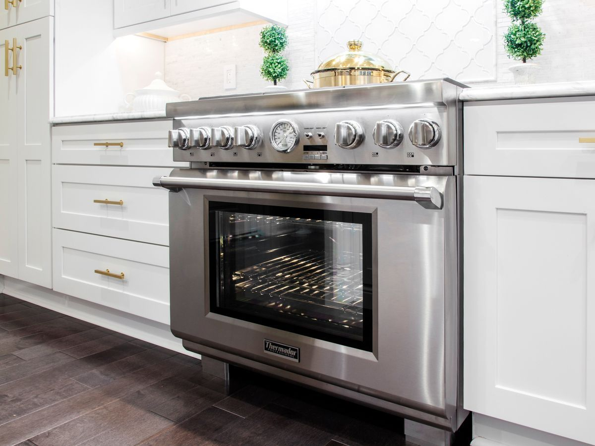 Thermador 36 Inch Range Side Shot With Oven Light On And Gold Accents In Kitchen Thermador 36 Inch Gas Range Kitchen Range Hood