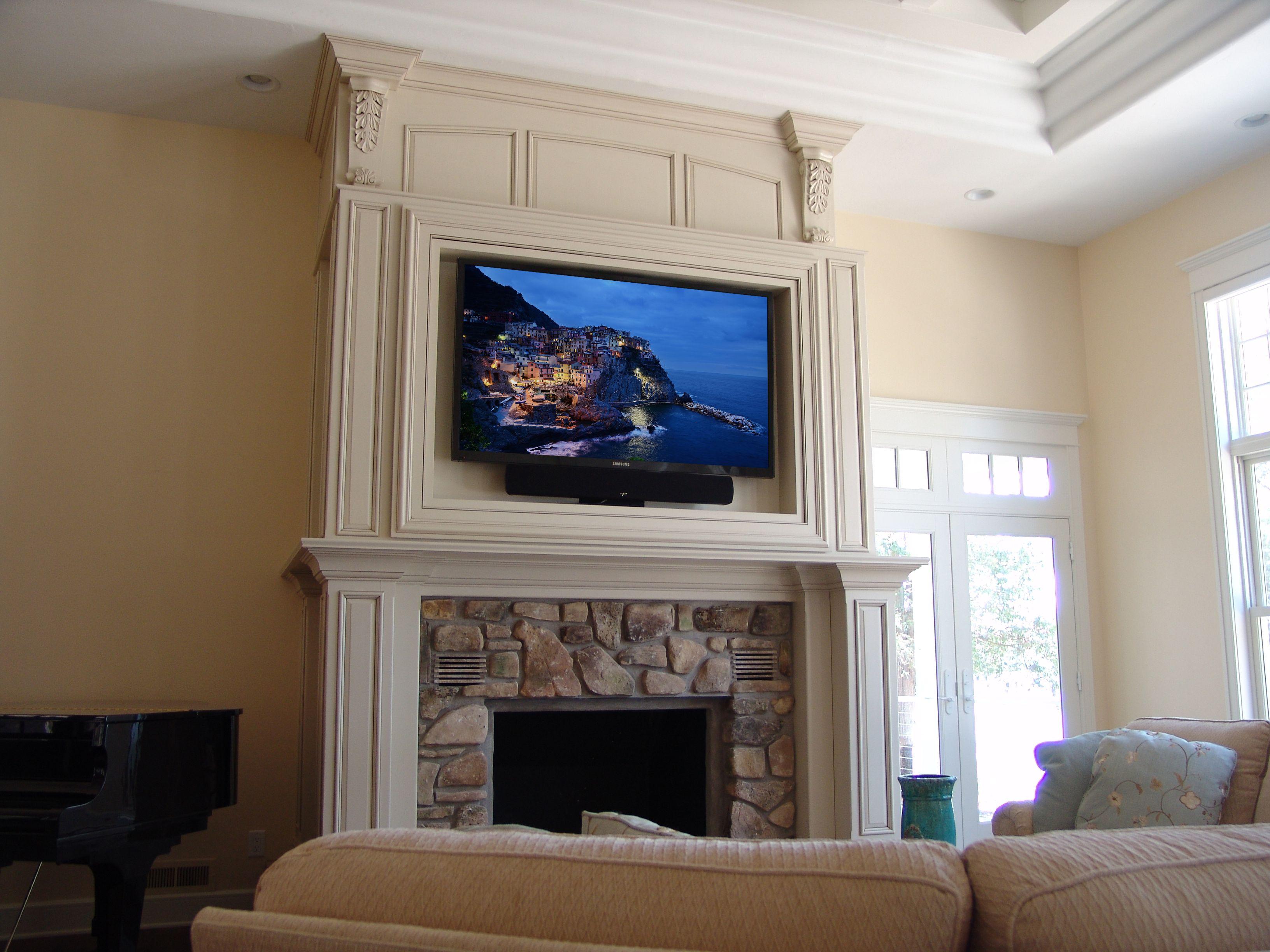 flatscreen tv and soundbar over a stone fireplace with wood surround rh pinterest com