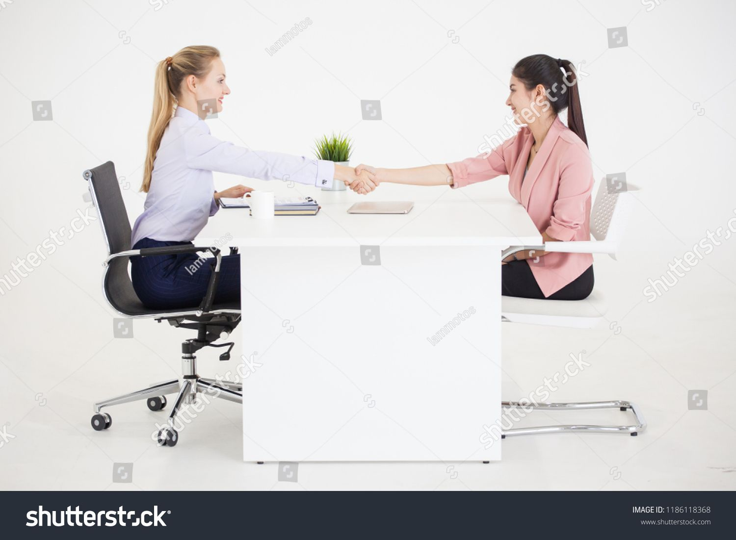 Two Businesswomen In Suits Sitting Between The Table Handshaking Of Deal On White Background Human Resources Ma Business Women Human Resources Template Design