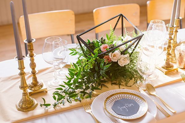 Geometric centerpiece overflowing with roses and greenery