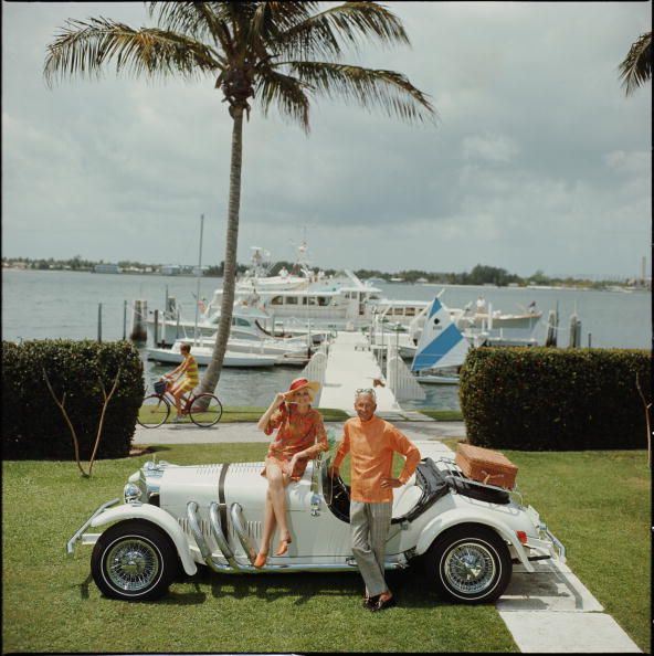Title:All Mine   Caption:Jim Kimberly and his wife, with his white sports car and white boats moored on Lake Worth. A Palm Beach socialite, he acts as Honorary Consul of Jordan.       Artist:Slim Aarons  Date:1968