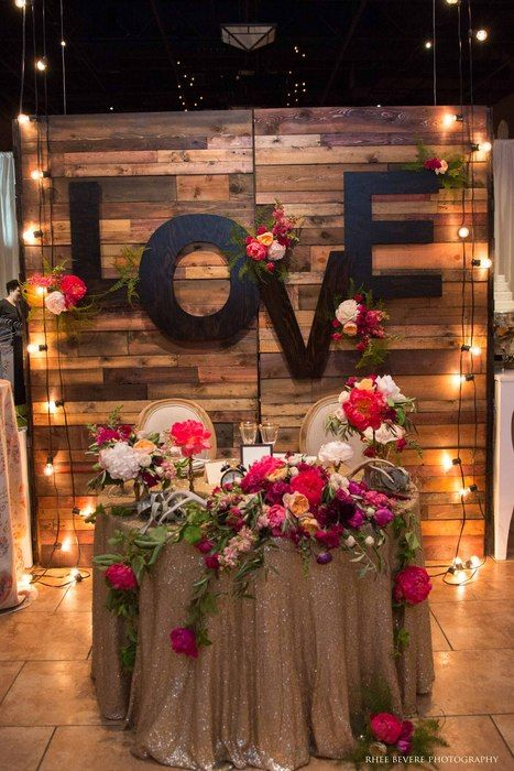 A sweetheart table one could only dream about! Nicole Ha Design styled our Reclaimed Barn Wood Walls, Love monogram letters, and market lights  Napa Valley Linens sequin tablecloth adds the perfect am