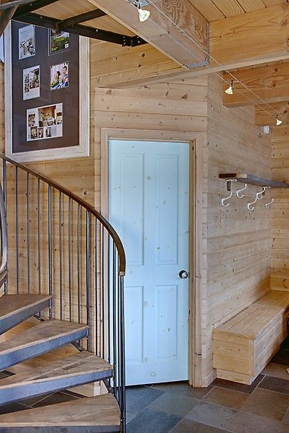 Clean and simple entryway with cedar planked walls and a curving stairway. Discovered on Porch.com