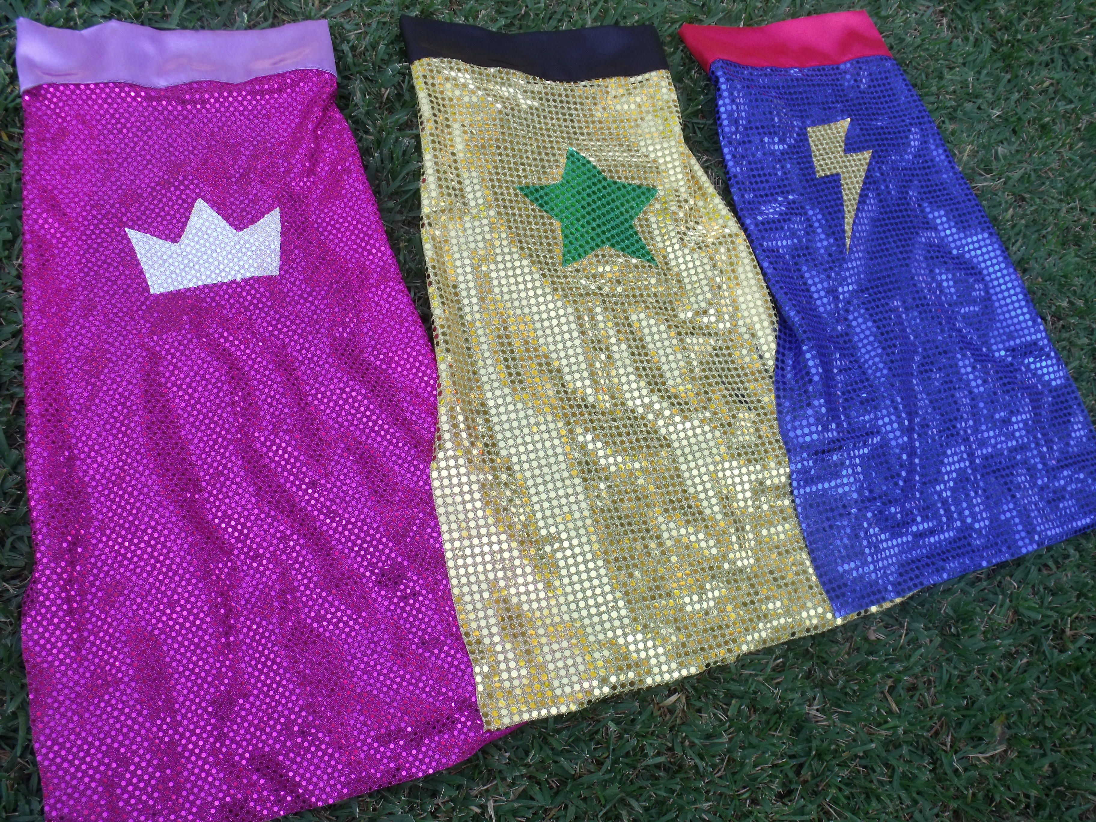 Easy superhero capes made for the Arts & Craft stall of the School Fete. Cut disco sequin into long rectangles - no hemming needed - and put on a satin collar that attaches with velcroe at the ends, and use a double-sided interfacing to iron-on a symbol like a star or lightening bolt.