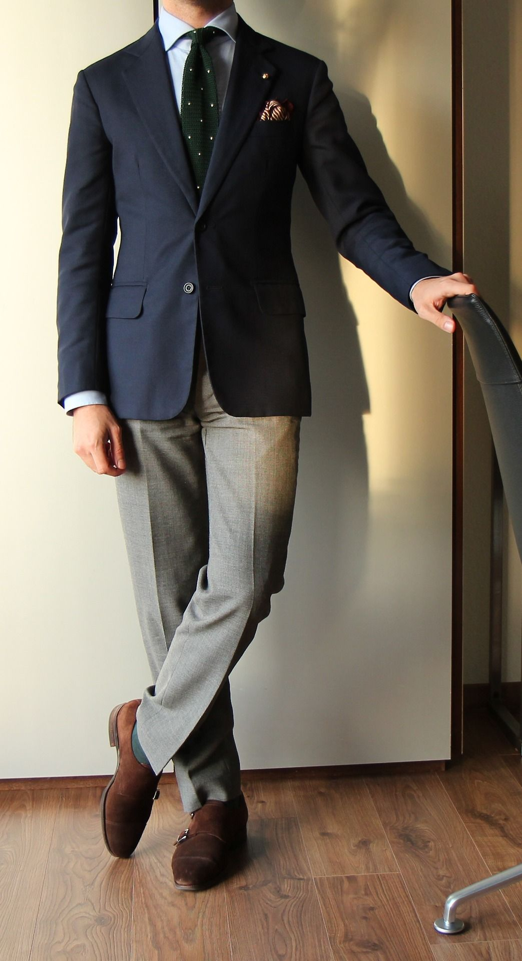 Navy jacket, light blue shirt, green knit tie with white