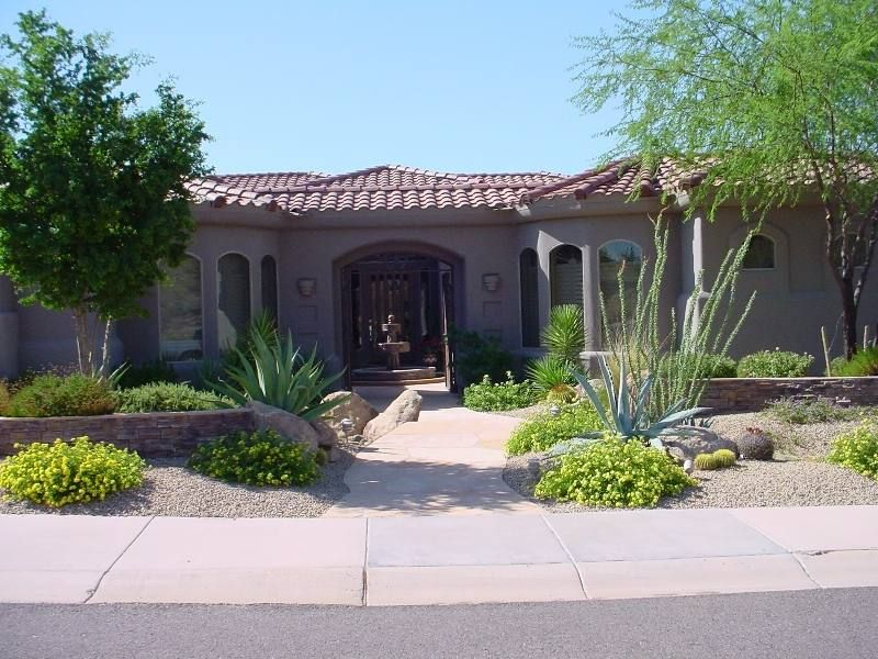 a well balanced front yard design with stone walls and shrubs welcome visitors to a beautiful