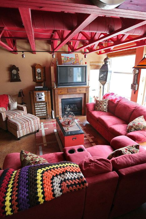 Fun red room with red couch and ceiling frames.