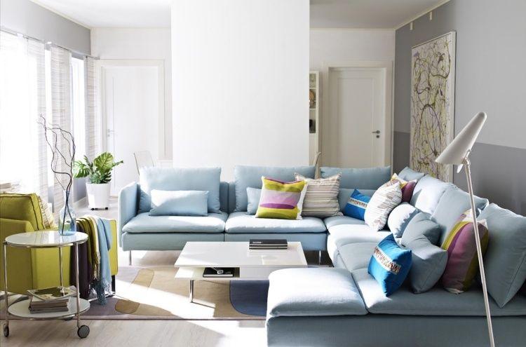 grand canapé en bleu clair décoré de coussins bariolés, fauteuil jaune et table d'appoint métallique