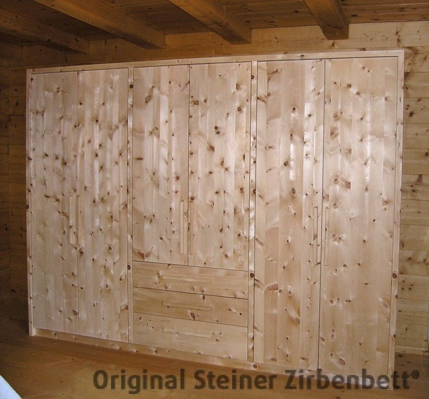 Schlafzimmerschrank aus Zirbenholz vor Zirbenholzwand