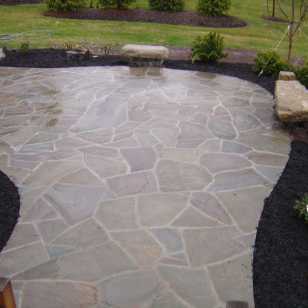 This Irregular Flagstone Patio Is Wet Set With Mortar Joints Specially Selected Boulders Are Used As Natural Sto Patio Stones Flagstone Patio Bluestone Patio