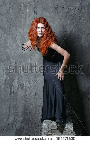 Red-haired vampire girl with red lips posing in urban twilight @shutterstock