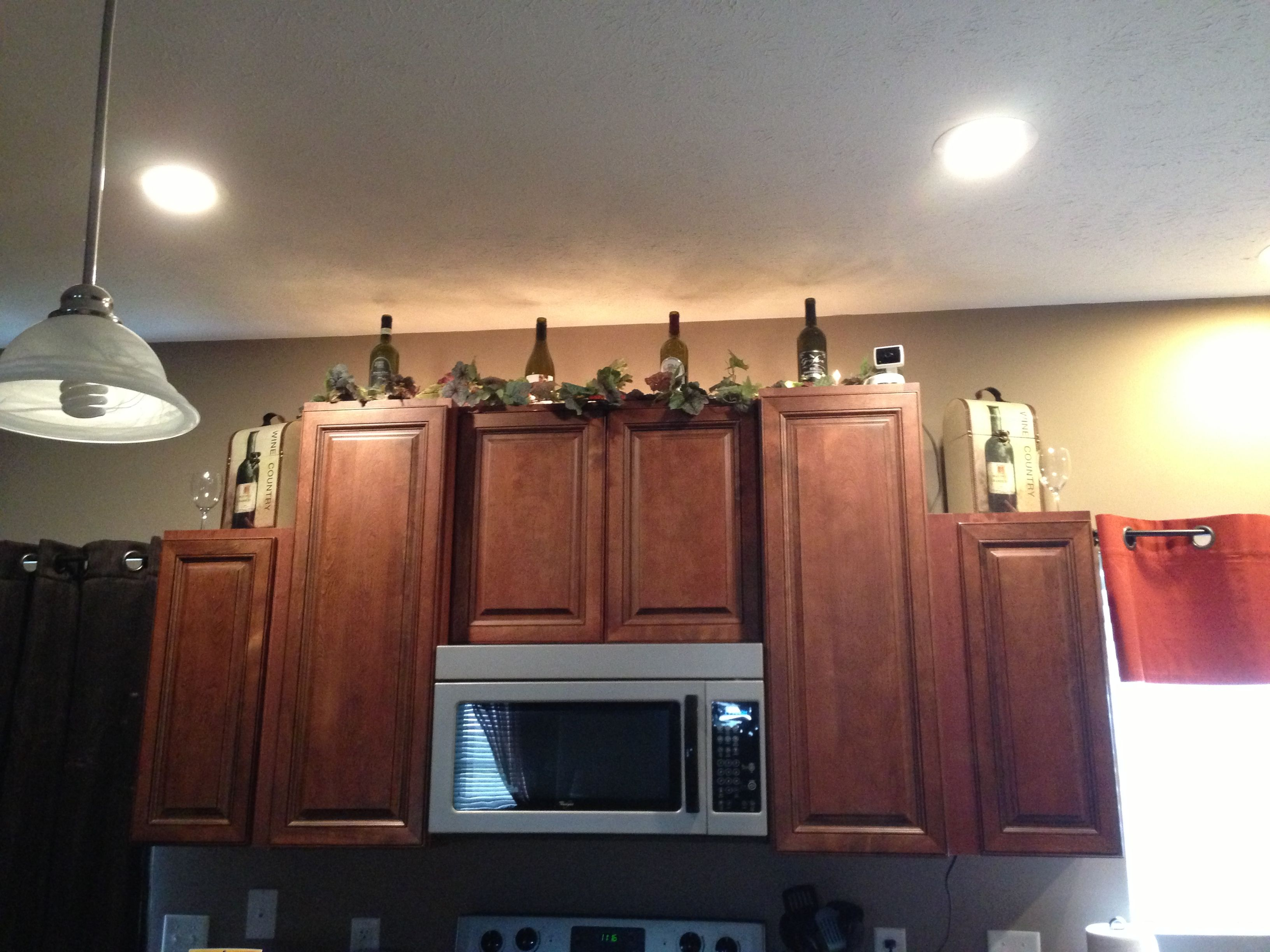 Wine bottle kitchen cabinet decorations home decor ideas for Above cupboard decoration ideas