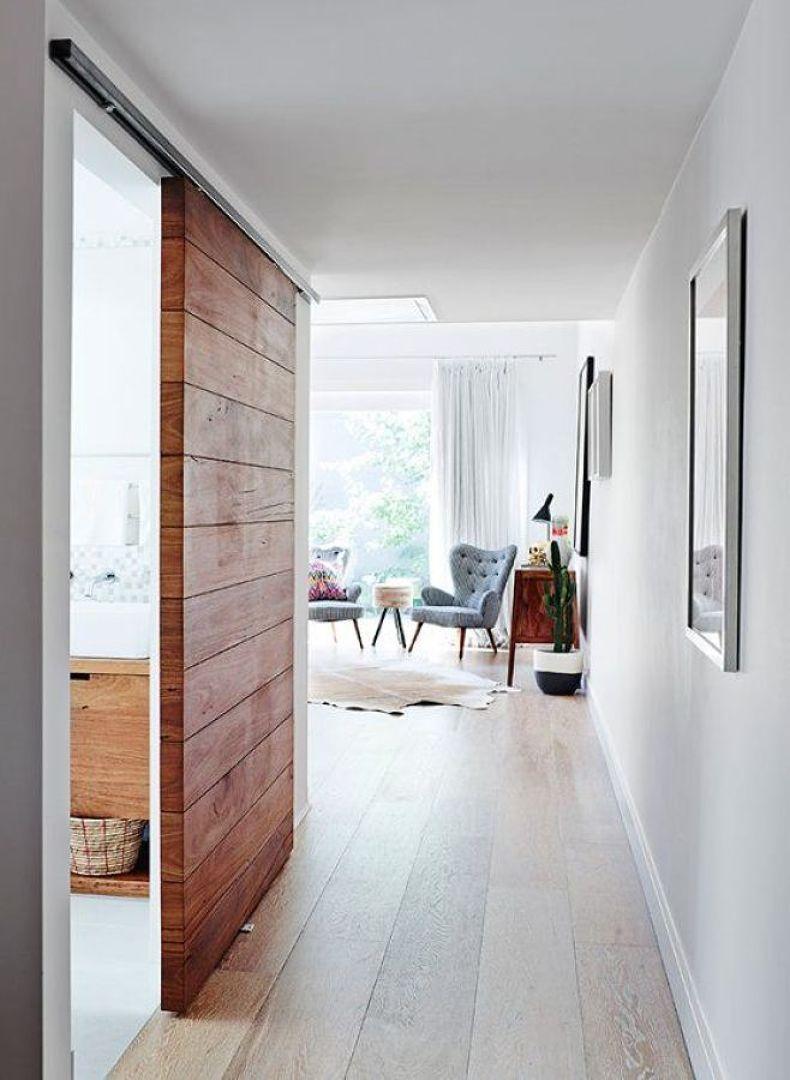 Puerta corrediza de madera con riel a la vista banys for Riel para puerta corrediza