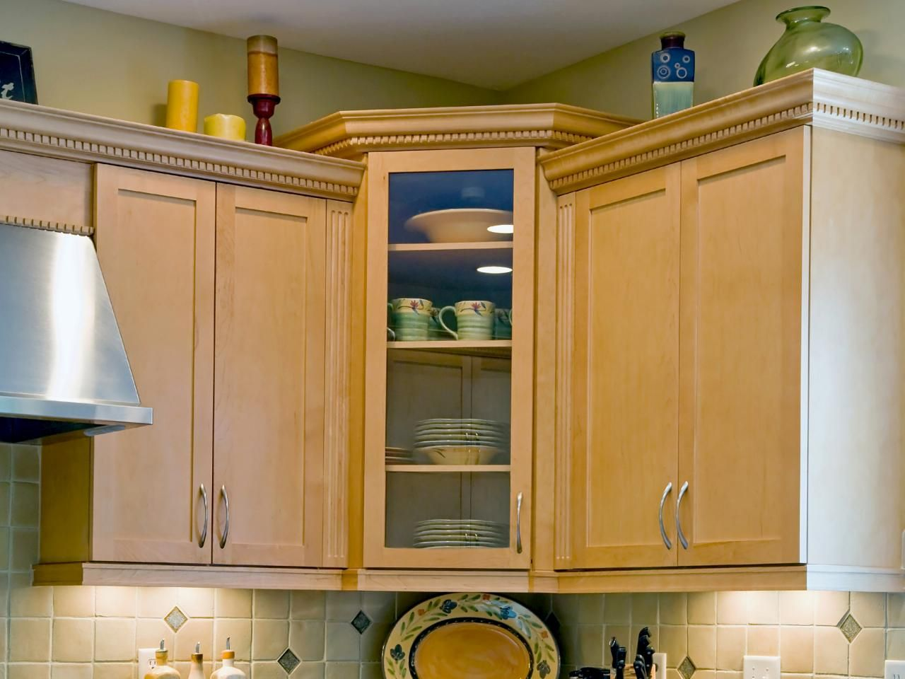 A Tight Shot Of Light Colored Wood Corner Kitchen Cabinets With Dishes  Stored Inside.