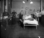 Interior view of a fire station in Denver Colorado men by iron beds pull pants