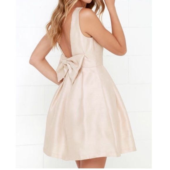 Lulu's Bow Me A Kiss Beige Backless Bow Dress Shimmery beige cocktail dress with bow detail at lower back. Worn once to my rehearsal dinner. Lined with satin and tulle to keep the skirt shape. Dress is sold out online, retails for $68. There's one tiny stain on the front that's barely noticeable (pictured) and honestly it was there when I opened the package- I didn't see it until I put it on for my rehearsal dinner (too much other wedding excitement going on for me to worry about it!) Lulu's…