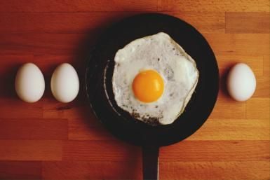 Directly Above Shot Of Eggs And Fried Egg In Frying Pan On Table - Daniel Kormann/EyeEm/Getty Images