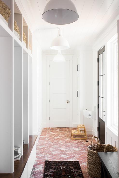 Clad In Red Herringbone Brick Floor Tiles This Stunning Long Mudroom Is Illuminated By Three White Industrial Mudroom Remodel Mudroom Flooring Mudroom Design