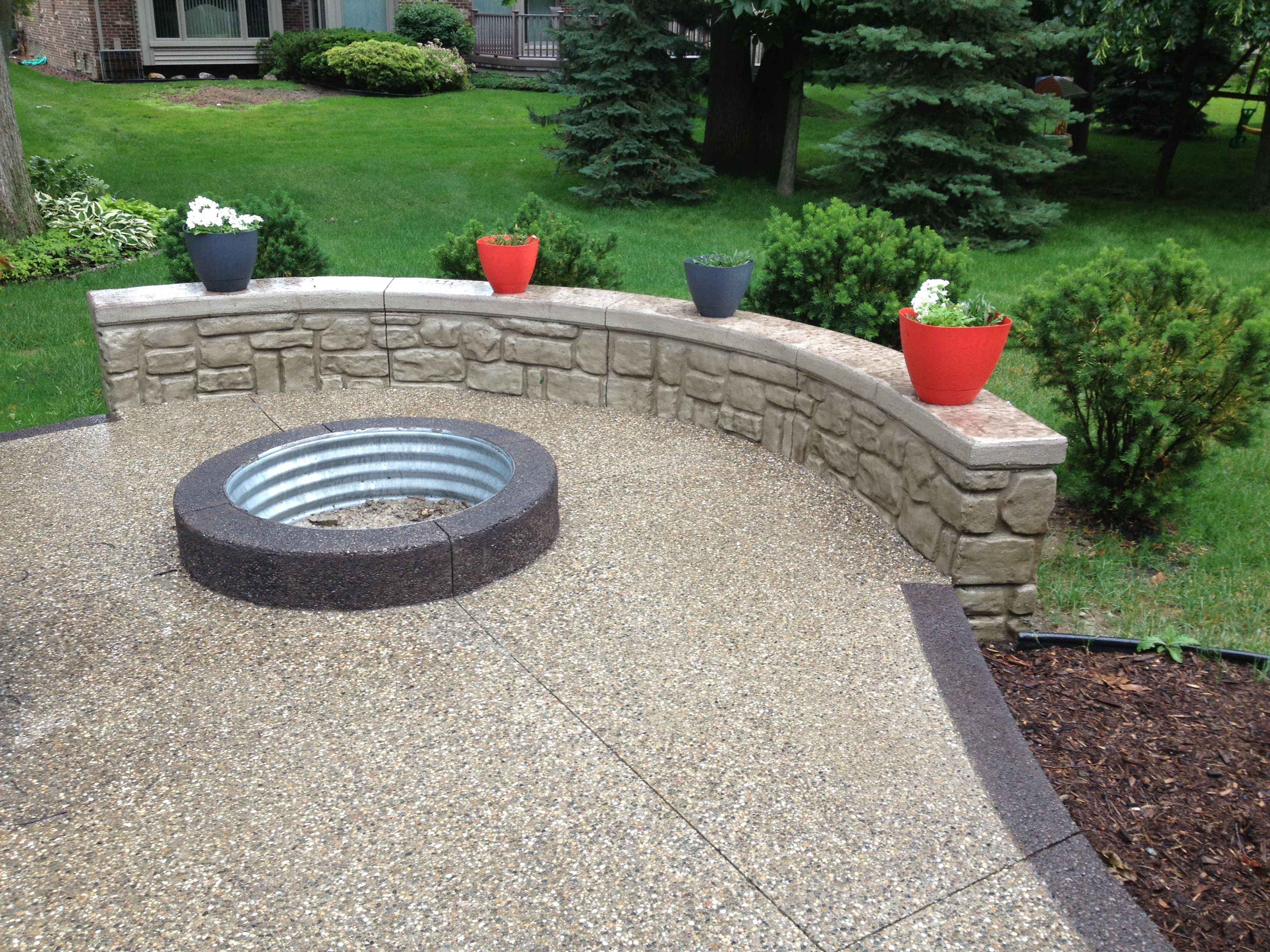 Exposed aggregate with pre fab fire pit ring and rock face for Concrete fire pit plans