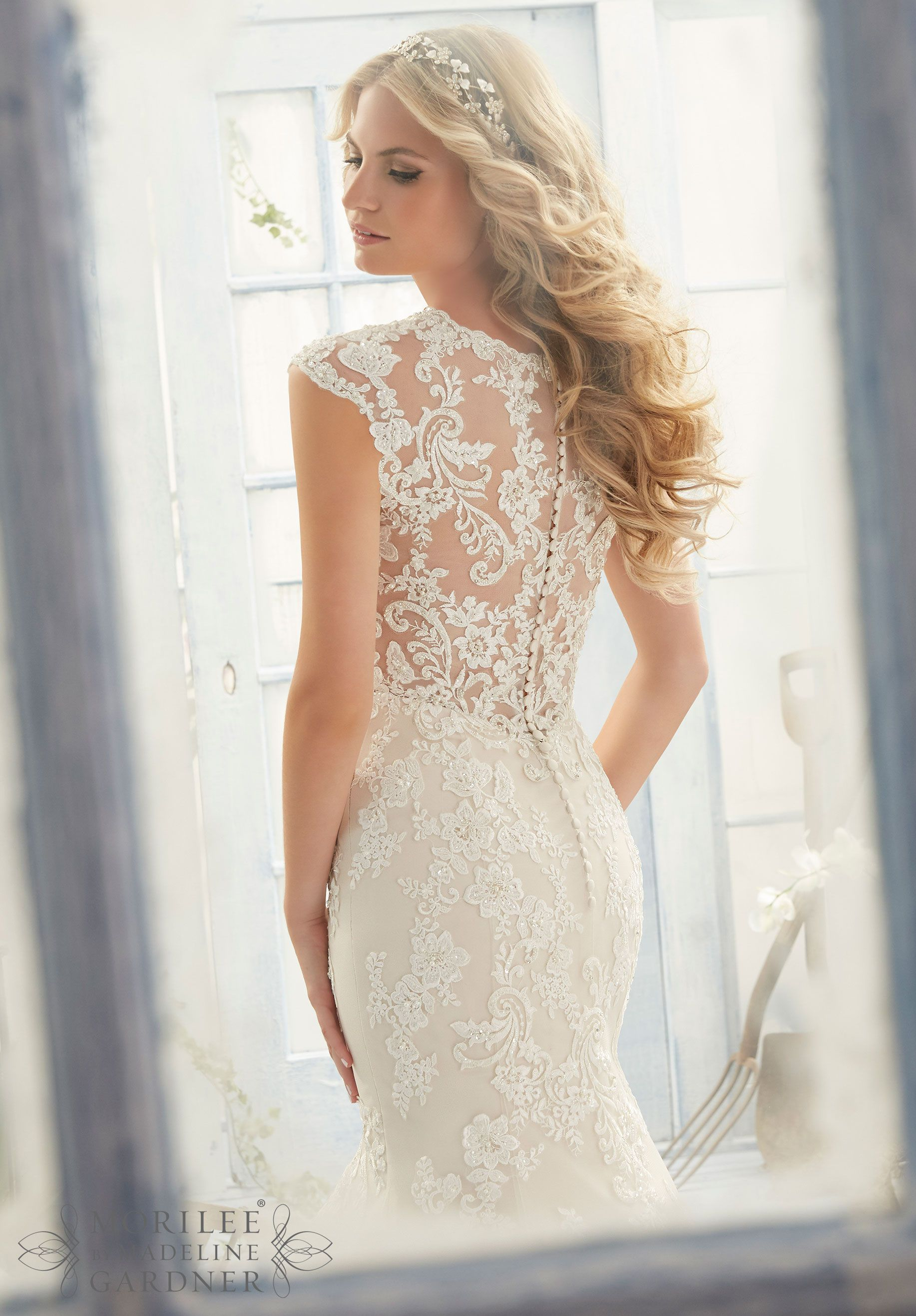 Trending Wedding Dress Crystal Beaded Embroidered Appliques and Scalloped Hemline on a Net Gown with Sheer