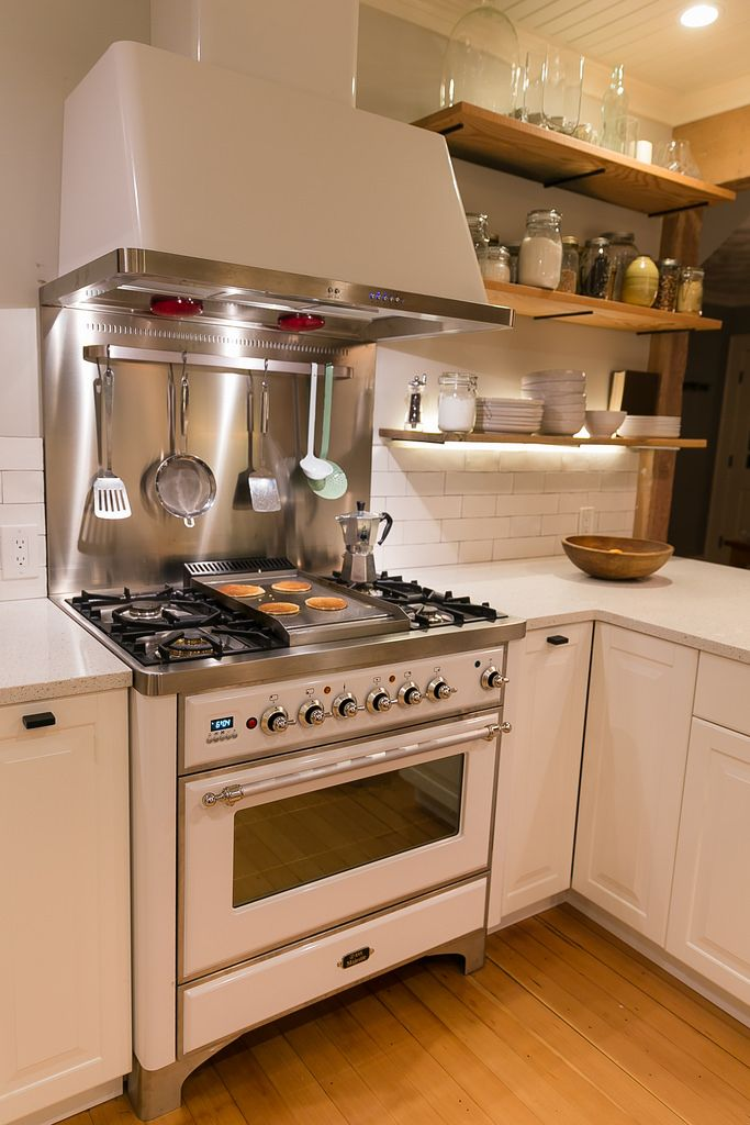 True White ILVE Majestic Range With Chrome Trim, Color Matched Hood And Stainless  Steel Backsplash.