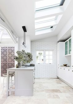 White kitchen - modern but warm with travertine tiles