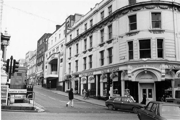 """""""This photograph shows an early Virgin Records shop at the western end of North Street. Nearby the Regent Cinema is closed awaiting demolition. Both of these buildings were demolished in 1974 and the site is now occupied by Boots the Chemists. A blue police box can be seen above the now filled-in public toilets under the clock tower."""" Royal Pavilion and Museums Brighton and Hove."""