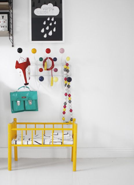 Bright yellow dolls bed. Graphic poster. Colourful rack. 50th suitcase