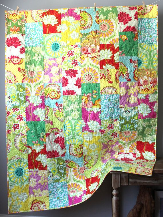 This beautiful lap quilt is completed and ready to ship to you! This modern, bright lap quilt features fabrics from the out of print Pop Garden collection. The color palette is unique and joyful, with beautiful vibrant yellow, and spring green with pops of red, fuchsia, and orange. There is nothing else quite like this combination of beautiful, large scale florals! It would be the perfect accent to add some summer color to celebrate the season. It is professionally quilted in white thread…