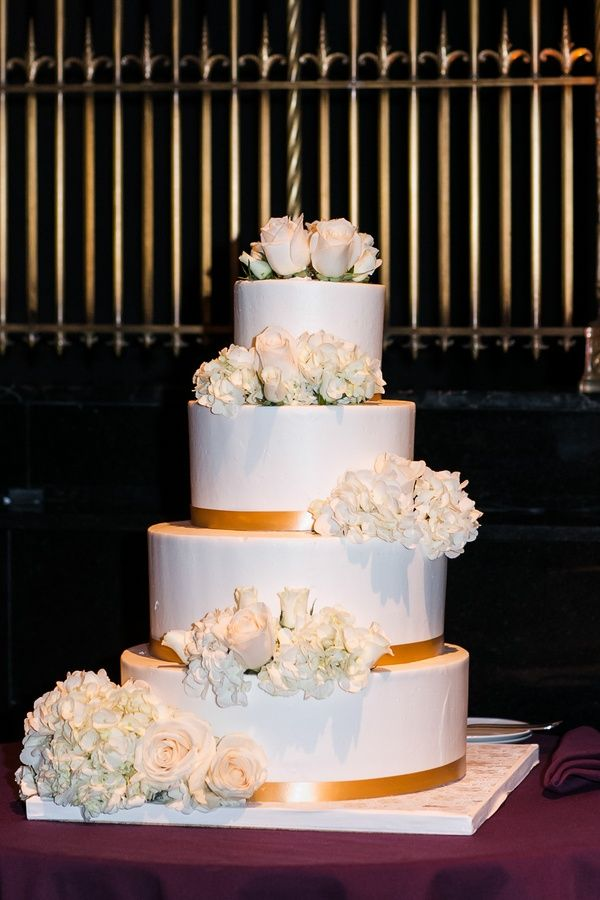 Four Layer Wedding Cake With Gold Ribbon And Fresh Hydrangea Rose Flowers