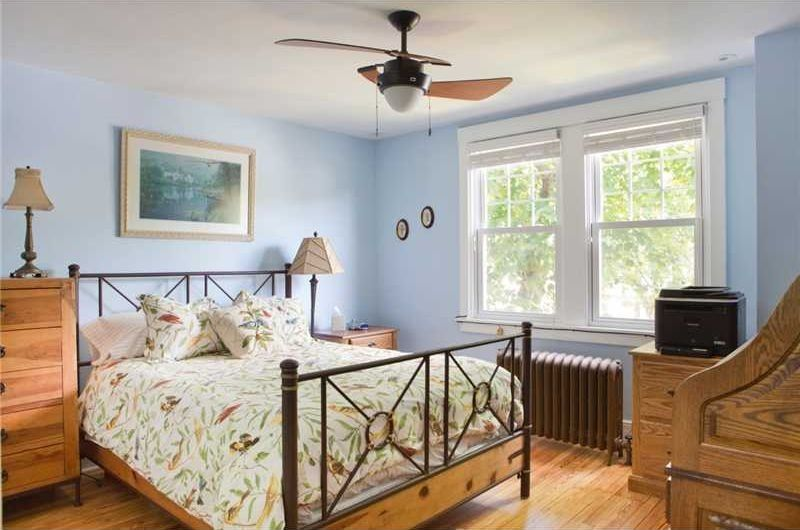 Dieses Schlafzimmer Erreicht Einen Hellen Und Luftigen Look Mit Baby Blaue  Wände Und Große Weiße Gerahmte Fenster.