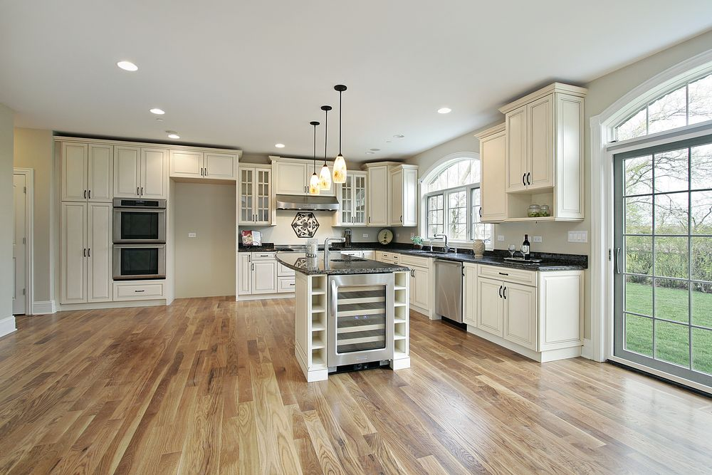 Wunderbar Expansive Kitchen Featuring White Throughout, Plus Light Hardwood Flooring  And Island With Built In