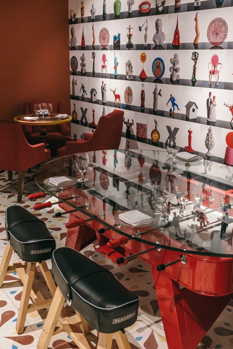 Swanky foos ball dining table meets playful wallpaper decor
