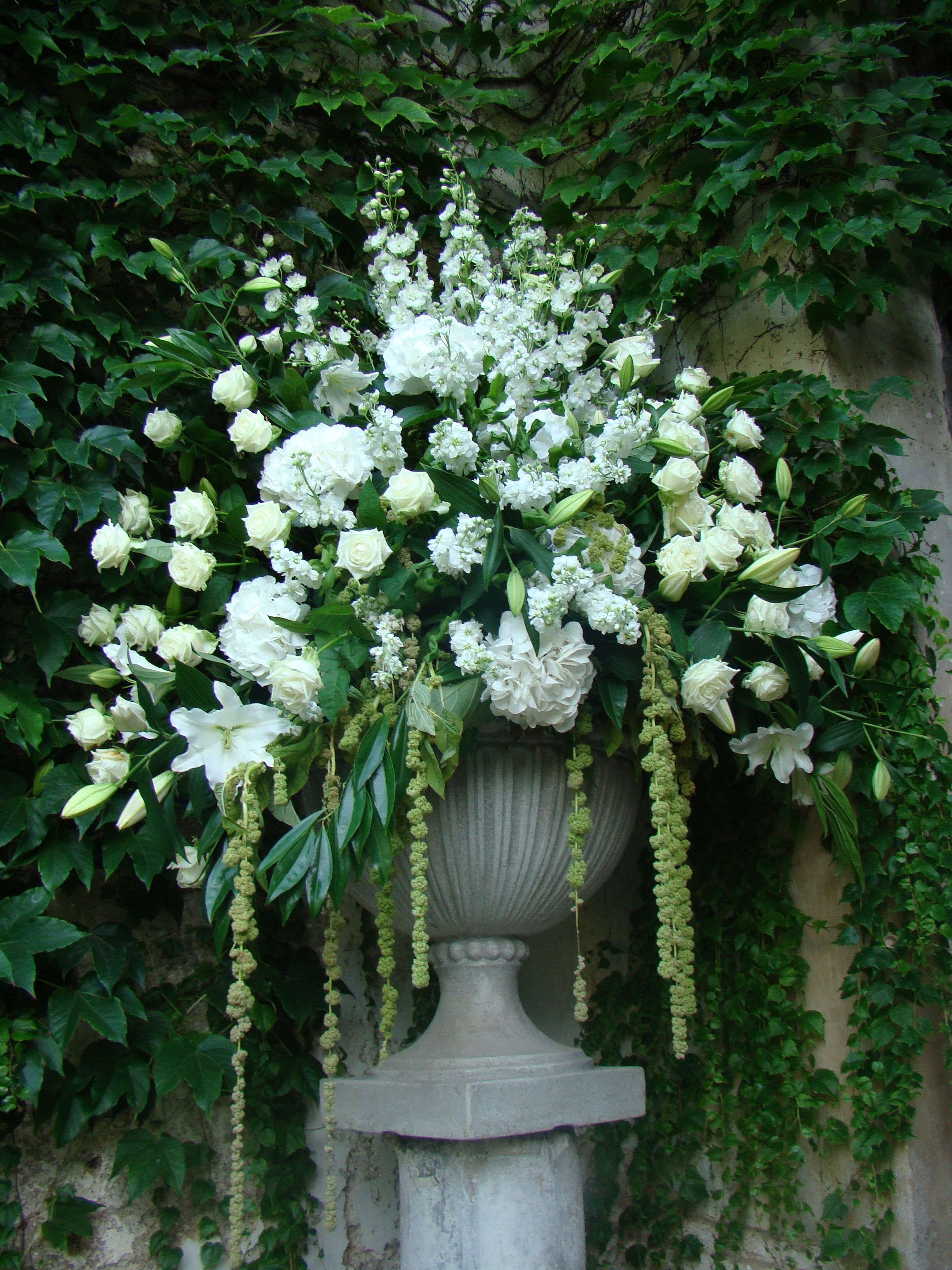 Urn with white roses, stocks, delphiniums, hydrangeas and