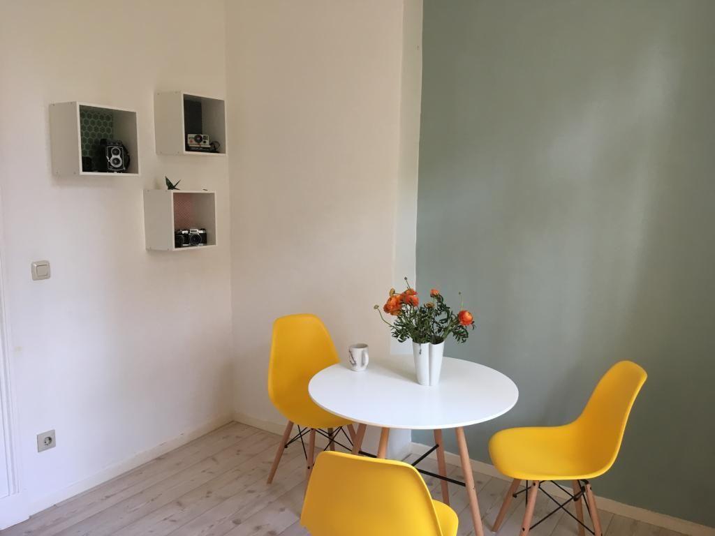 essbereich mit rundem tisch, grüner wand und gelben stühlen, Wohnzimmer dekoo
