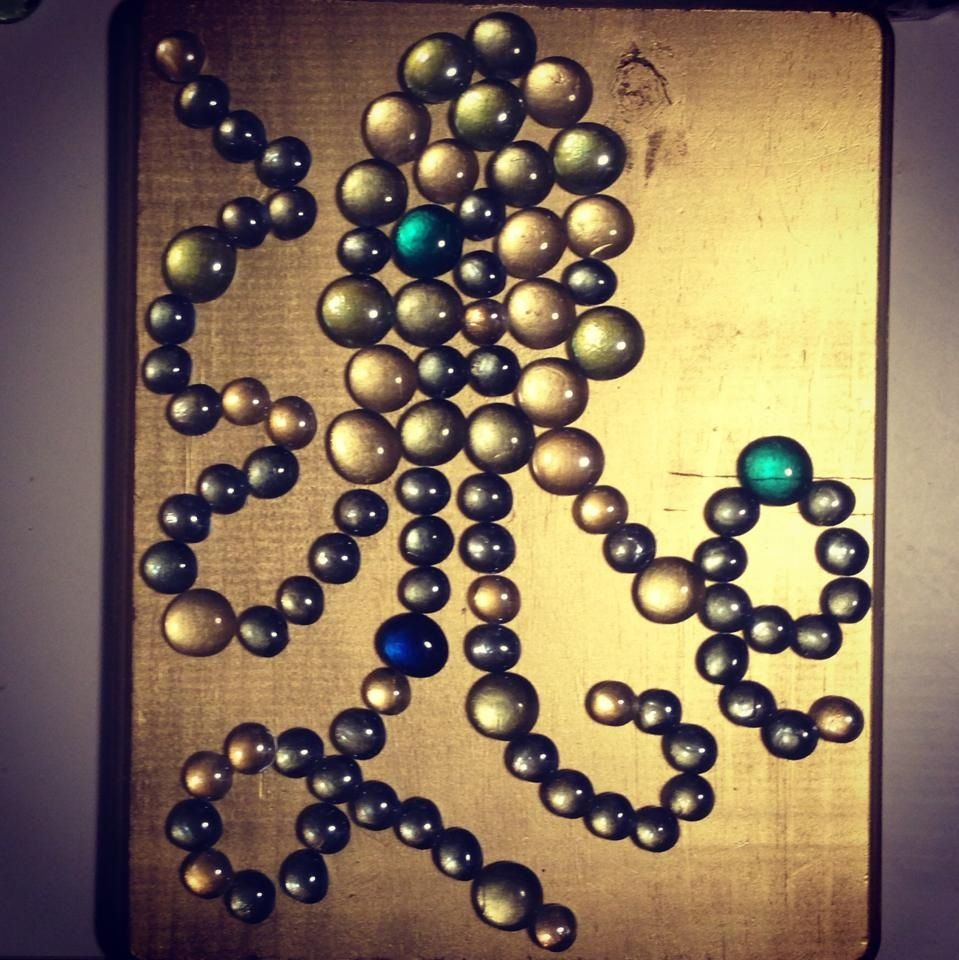 Flat glass marbles crafts - Flat Glass Marbles Shaped Into An Octopus Glued On To A Piece Of Gold Spray